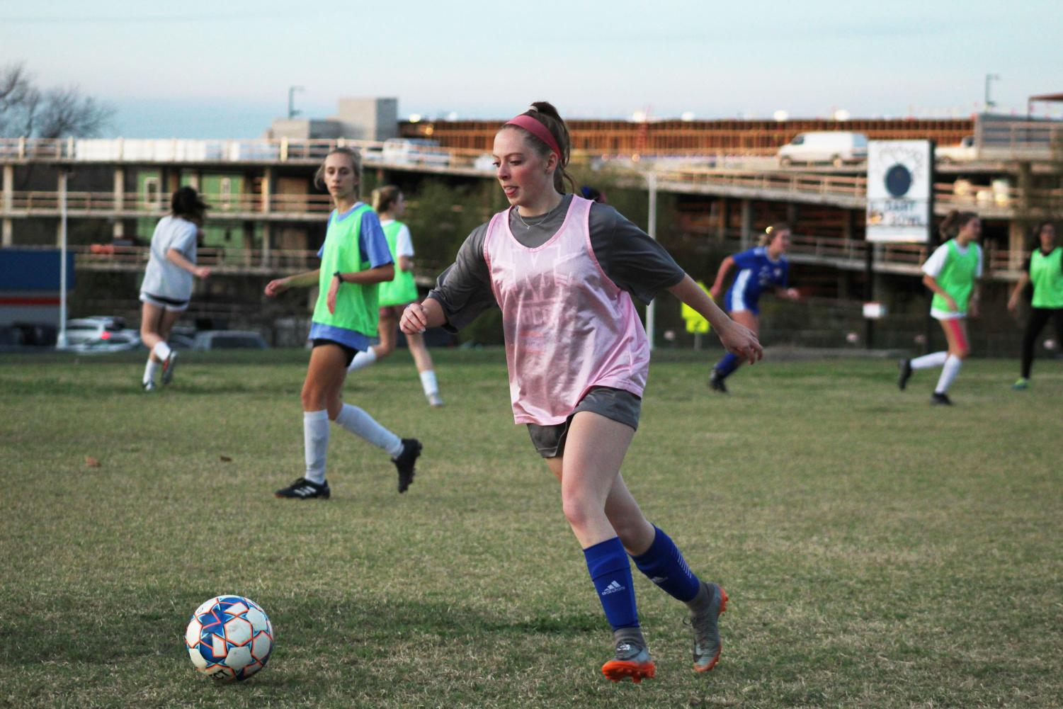 "During the last day of soccer tryouts on Wednesday Dec. 4,  junior Avery Miller dribbles down the field looking to pass to an open player. ""I want [us] to go to playoffs again,"" Miller said.  ""And I want [us] to try and make first in district [and] also beat Dripping Springs again."" Last year the Knights became the first varsity team to beat Dripping Springs in district play. Photo by Risa Darlington-Horta."