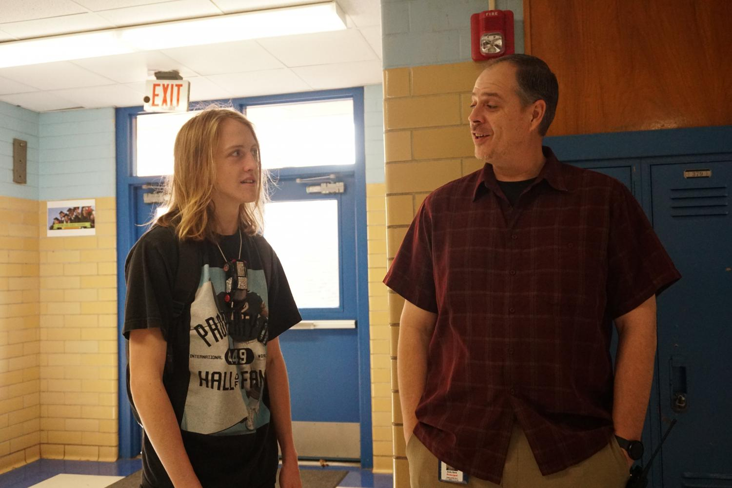 """Assistant principal Andy Baxa talks to junior Emmett McCormick in the main hallway where he supervises during passing period Monday morning. """"What I would encourage [students] to do is do whatever you want to do, do whatever you feel passionate about, """" he said. """"Good things will happen if you follow your passion.""""  Photo by Elisha Scott."""