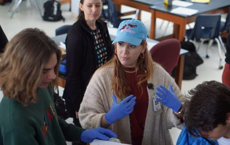 """Baughman explains part of the procedue of a lab in forensics to senior Sam Sherrill. """"[Baughman] believes in each of her students and gives them all her time and energy in helping them to be successful,"""" senior Ella Irwin said. Photo by Dave Winter."""