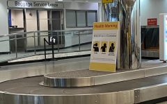 A sign at baggage claim at the LaGuardia Airport in Queens illustrates the common symptons of coronavirus so that customers can be aware of them while travelling. Photo by Mia Terminella.