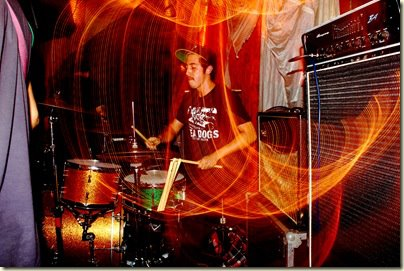 "Daniel Vega plays the drums with his band Zlam Dunk during the band's third tour. Vega said he wasn't sure where and when the photo was taken but his best guess was that it was in Philadelphia in 2011. ""It was the longest tour we ever did,"" Vega recalled, ""roughly five weeks on the road, living in a van and crashing on floors. Best time of my life, other than getting married and teaching at McCallum obviously."" The extended spring break gave the math teacher the chance to realize an album project that has been four years in the making. The album, ""Decade"" by Crooked Numbers, was released on April 1 (no fooling). Vega wrote all of the lyrics and music for the album and compiled drums and bass recordings from four years ago along with more recent guitar, keyboards and vocal recordings. ""I have been playing drums most of my life … and this album has been a long time coming,"" Vega told MacJournalism. ""I've been working on the songs since around 2016, but when you have a full-time job and a life, music kind of gets put on the back burner."" Photo by Danny Garcia (probably)."