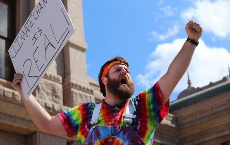 """TRUE COLORS: Austin resident and climate activist Woodstock James stands above the crowd at the Austin Climate Strike holding a sign that reads, """"Climate change is real."""" Disappointed by the lack of action from the Texas legislature in the face of the impending climate crisis, James hoped to spur lawmakers to action by joining the strike. """"It's a huge issue that we should all be paying attention to right now,"""" he said. """"The people who need to listen to us are being paid not to, and it's very unfortunate."""" Reporting by Samantha Powers. Photo by Risa Darlington-Horta."""