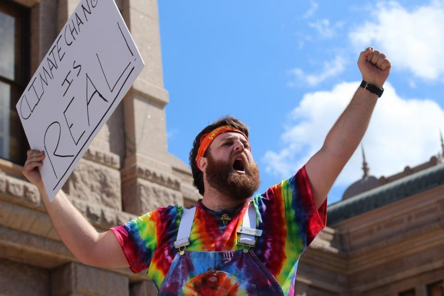 "TRUE COLORS: Austin resident and climate activist Woodstock James stands above the crowd at the Austin Climate Strike holding a sign that reads, ""Climate change is real."" Disappointed by the lack of action from the Texas legislature in the face of the impending climate crisis, James hoped to spur lawmakers to action by joining the strike. ""It's a huge issue that we should all be paying attention to right now,"" he said. ""The people who need to listen to us are being paid not to, and it's very unfortunate."" Reporting by Samantha Powers. Photo by Risa Darlington-Horta."