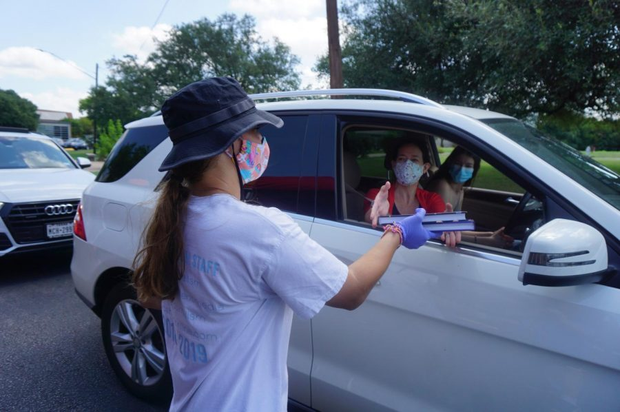 Rising junior Samantha Powers waits behind the wheel as rising senior Lindsey Plotkin hands Katharine Powers, Samantha's mom, two yearbooks during the yearbook staff's curbside distribution on Friday in front of the school. Samantha Powers drove because she got her driver's license the day before. Yearbook students wore facial masks and nitrile gloves as they distributed books. The book delivery was delayed to late summer because Balfour, the Dallas-based publisher, was closed for nearly two months and because students had to complete the yearbook remotely after the campus was closed on March 13. Photo by Dave Winter.