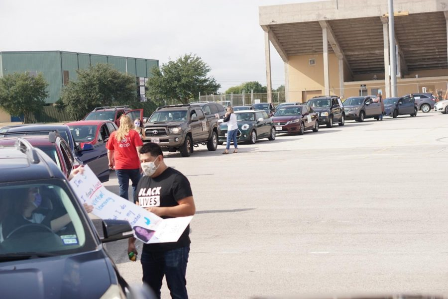 The rally, organized by Education Austin, began at two separate locations at Burger Stadium and Nelson Field, where cars then caravanned to the Southfield headquarters. Photo by Alysa Spiro.