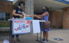 With the help of League of Women Voters Club volunteer Stephanie Land, senior Vanessa Lee registers to vote during the curbside voter registration drive in front of the main entrance of the school on Sept. 18. The club registered 10 voters (nine students) during the drive that day.