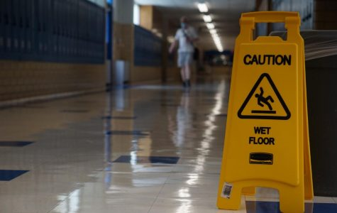 A caution sign stands in an empty hallway on the Friday to end the first week of school. So far all learning has been virtual, but some students will return to campus starting Oct. 5.
