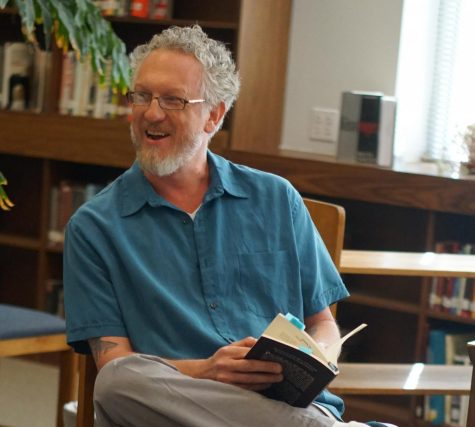 Myers reads original poetry at an early morning faculty poetry sharing session in the Mac library on April 24, 2018.
