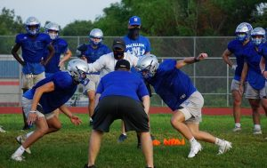Athletic teams such as the football team shown here are following safety protocols such as wearing facial masks and practicing social distancing during weight training and team exercises, but sports, especially football, volleyball and basketball,  require contact and close proximity between athletes, which increases risk of exposure to COVID-19.