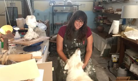 Carey West sits in her garage studio with her dog, Lily.  Since quarantine has started, Ms. West has established her workspace in her hot but functional garage.  Though it