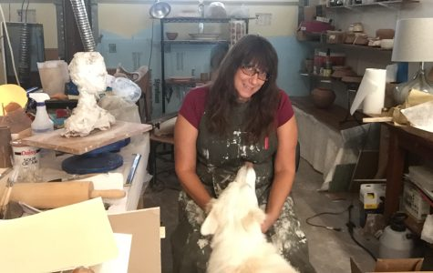 Carey West sits in her garage studio with her dog, Lily.  Since quarantine has started, Ms. West has established her workspace in her hot but functional garage.  Though it's not a perfect studio, she thinks it's important to relate with her students on the same level.