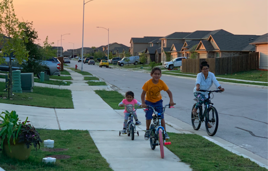 Taking a ride around their neighborhood,  Telvi Altamirano Cancino and her children enjoy their evening family time. Photo courtesy of Altamirano Cancino