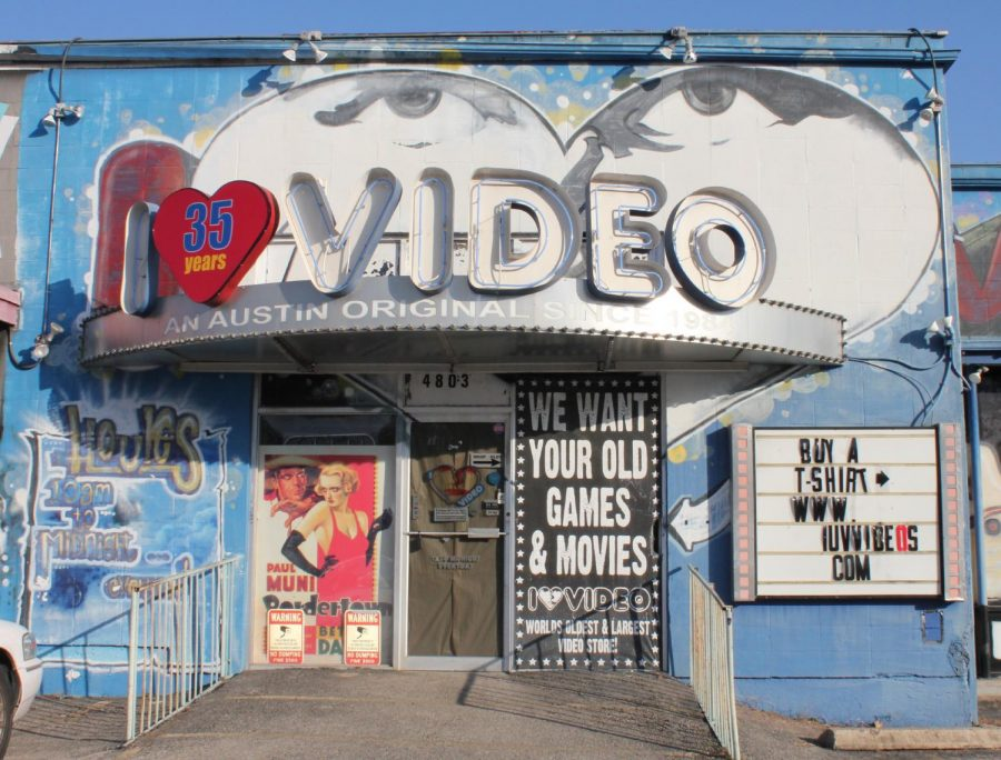 The I Luv Video storefront faces a nearly empty parking lot after closing down for business. The art-covered walls and colorful exterior reflect the friendly, creative atmosphere inside. While the store was open, staff were always ready to help customers find the films they wanted inside the