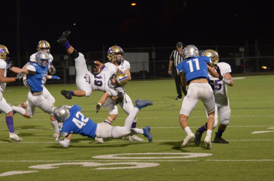 Junior safety Jake Hissey upends a Mustang ball carrier in the first half of Thursday's game. Defense was the deciding factor in the game. Not only did the Knights shut out the Mustangs, but they also scored a touchdown on defense and created three turnovers.