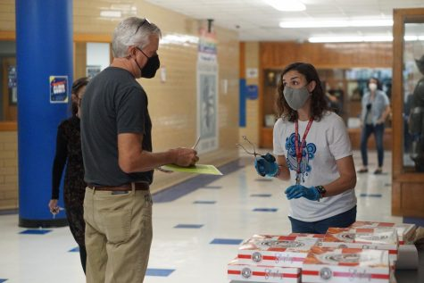 Wearing surgical gloves and using metal tongs, new facilities manager Camille Nix asks math teacher Scott Pass if he wants a glazed doughnut, a chocolate glazed doughnut or both. The sweet Friday treats came courtesy of the Mac administration.