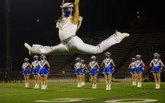 Senior Blue Brigade co-captain Matthew Vargas leaps during the Dec. 11 halftime show, a field pom dance to