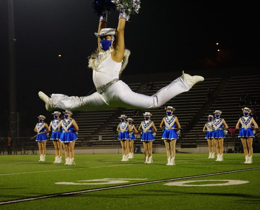 Senior Blue Brigade co-captain Matthew Vargas leaps during the Dec. 11 halftime show, a field pom dance to