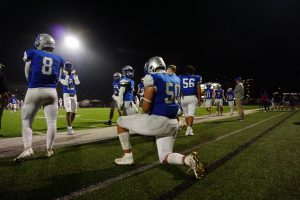 """Senior lineman Charlie Pecina kneels, taking in his last few moments on the field at House Park as a McCallum football player. Pecina said the team was optimistic heading into Fridays bi-district playoff game. """"Going into the game I knew we had to win or else it would be my last game in a McCallum jersey, but I felt confident because the coaches and the team felt like we had a good week of practice."""" The game was a tough one as the Knights lost several players to injury or penalties. Despite the attrition, Pecina said he and his teammates left all they had on the field. Pecina made one of the games best plays for the home team, a first-quarter interception the extinguished a Patriot scoring threat. """"Things didn't go our way with calls and injuries, but that doesn't matter. We still played our game and still put the most effort we could into the game."""" Although the game was a loss, Pecina focused on the progress he, and his teammates have made. """"Even though we lost I was proud of how far we came from only winning one game our freshman year to having a winning season and making the playoffs."""""""