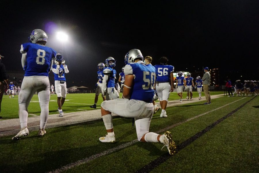"""Senior lineman Charlie Pecina kneels, taking in his last few moments on the field at House Park as a McCallum football player. Pecina said the team was optimistic heading into Friday's bi-district playoff game. """"Going into the game I knew we had to win or else it would be my last game in a McCallum jersey, but I felt confident because the coaches and the team felt like we had a good week of practice."""" The game was a tough one as the Knights lost several players to injury or penalties. Despite the attrition, Pecina said he and his teammates left all they had on the field. Pecina made one of the game's best plays for the home team, a first-quarter interception the extinguished a Patriot scoring threat. """"Things didn't go our way with calls and injuries, but that doesn't matter. We still played our game and still put the most effort we could into the game."""" Although the game was a loss, Pecina focused on the progress he, and his teammates have made. """"Even though we lost I was proud of how far we came from only winning one game our freshman year to having a winning season and making the playoffs."""""""