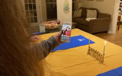 """FESTIVE FACETIME- After reciting the Hanukkah prayers and lighting her menorah the first night of Hanukkah, Carolyn Schwarz talks with her parents, John and Rhoda Schwarz over Facetime. Usually the Schwarzes would gather in-person to celebrate Hanukkah, but due to the safety concerns of coronavirus they decided to take part in the festivities virtually this year. """"Having older parents and knowing the health risks the virus could have on them made our holiday plans very clear"""" Carolyn said. """"We knew that physically getting together would not be a safe option this year."""" Carolyn celebrated the holiday at home with her husband and children while her parents celebrated with their dog, Winston. """"So much is different this year,"""" Rhoda said. """"It is a blessing that we can still celebrate with each other in some way."""""""