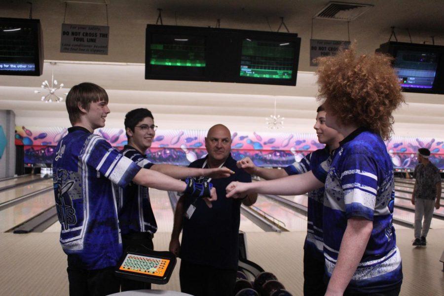 Seniors Miles Lee and Bruno Cioci, Coach Dave Stanton, junior Keegan Langley and senior John Pratt share a fist bump at a Dart Bowl match in January.