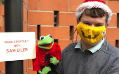 Taking a break at a holiday bazaar on Nov. 29, Sam Eiler poses with Kermit as he waits for people to arrive at The Holiday Happening, an outdoor lighting celebration where he was commissioned to draw portraits at the Carpenter Hotel.