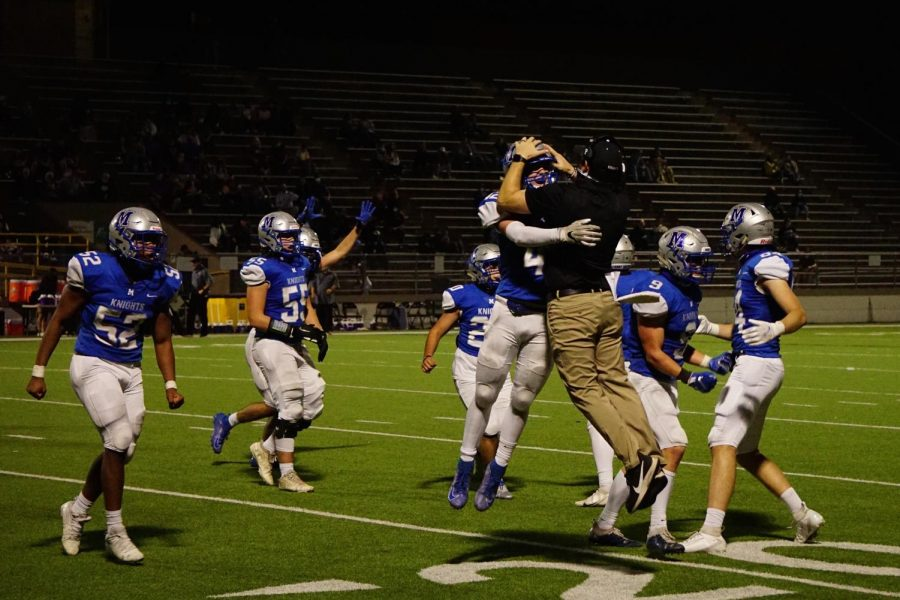 LEAPS AND DOWNS: Coach Chris Russell and junior safety Jake Hissey celebrate after Hissey's tackle forced a turnover on downs in the second half of the Knights' 14-0 victory over district opponent Marble Falls at House Park on Nov. 5. The Knight defense stifled the Mustang offense throughout the game and created three turnovers on downs in the second half alone.