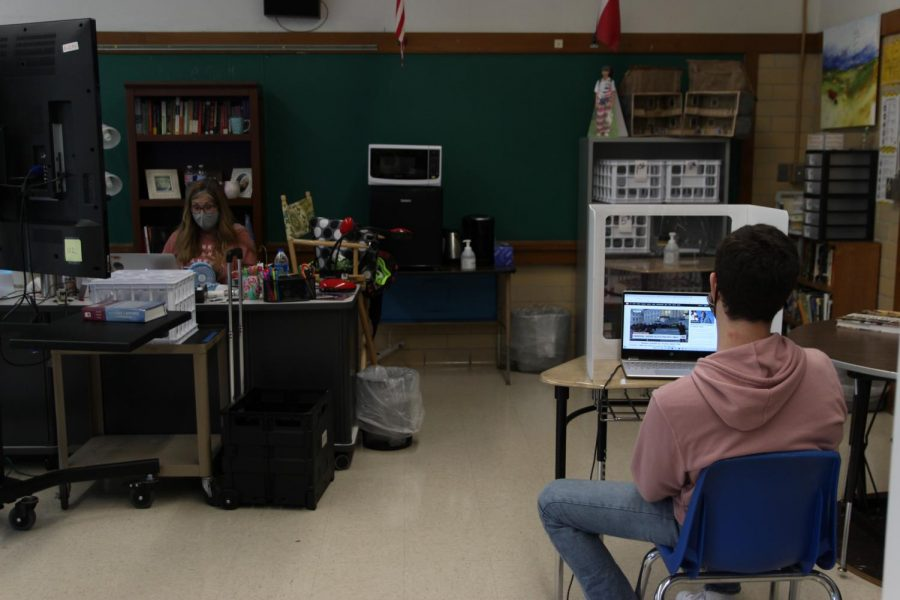 Senior Luke Lozano follows the news in Washington during Amy Smith's fourth-period AP Literature class on Wednesday.  There were 40 students on the Mac campus on Friday. The campus was closed today because of inclement weather.  Austin ISD had all teachers and student attend classes virtually. This afternoon Superintendent Elizalde urged families to select online learning in response to a rise in COVID hospitalizatons.