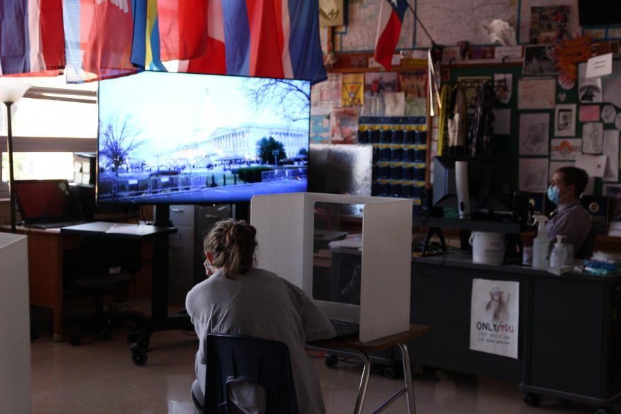 Social studies teacher Greg Anderson and his fourth-period georgraphy student freshman Lucy Minton watch the PBS News Hour coverage of the Capitol insurrection on Jan. 6.