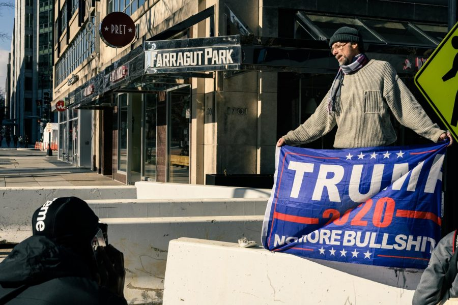 A Trump supporter brandishes a Trump 2020 flag during the inauguration ceremony of President Joe Biden and Vice President Kamala Harris, who defeated Trump and Vice President Mike Pence in the November election. Trump opted not to attend the inauguration ceremony, breaking a tradition of presidential attendance that dated back to 1869. Pence attended the ceremony. Photo by Geoff Livingston, accessed on Livingston's Flickr account. Reposted here with permission under a Creative Commons license.