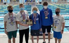 The region champions in the 200-yard medley relay race and their coach pose with their gold medals and championship plaque after the race. Senior Kyle Larson (backstroke), senior Izak Zaplatar (breaststroke), sophomore Luke Gordon (butterfly), senior Jack Hester (freestyle) and head coach Jeff Rudy.