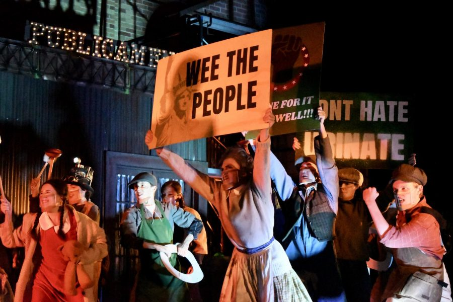 "WEE THE PEOPLE: Junior Amethyst Mellberg-Smith holds up a sign during a Urinetown scene involving a protest for the right to ""pee for free."" Mellberg-Smith thinks that the show is a commentary on the current political climate. ""It's totally political satire,"" Mellberg-Smith said. ""It's making fun of serious situations that are somewhat similar to things happening now, but in such a comedic and absurd way it really shows how messy politics and fighting for what's right can be."" Mellberg-Smith said that while being on stage for the first time in a year was a rewarding experience, her favorite part of the production was spending time with her friends. ""Finally seeing people every day made all of the hard work feel effortless,"" Mellberg-Smith said, ""and I can't wait to do it again!"" Reporting by Samantha Powers."