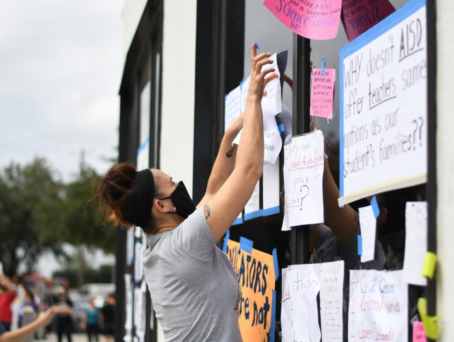 English teacher Nikki Northcutt tapes a flyer to the AISD Southfield building at a teacher rally on Sep. 26, 2020. Caravans of AISD staff organized by Education Austin drove to the district headquarters to protest campus re-openings and raise questions and concerns for the district.