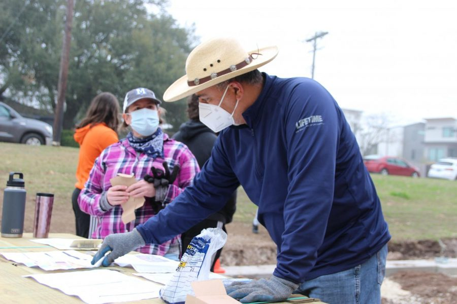 """Mr.Reyes looks over the plans for the outdoor stage with parent volunteer Nicole Wayman at the beginning of the community building day on Saturday, Feb. 6. Reyes says working on that stage was one of his proudest moments in the 15 years he's been on this campus. """"It was awesome to work with the parents and kids,"""" Reyes said. """"I remember after the dance show and Urinetown that night I was walking back to my car, and I was like """"This is what it means to serve your community."""""""