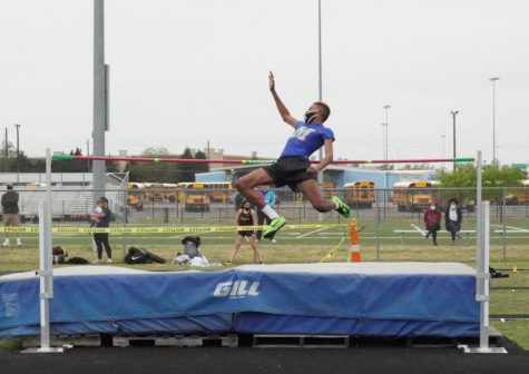 Senior O'Mari Hill leaps over the bar during the high jump early Thursday morning. He secured fourth with a jump of 5 feet, 8 inches, just making the cut for next week's Regionals meet.