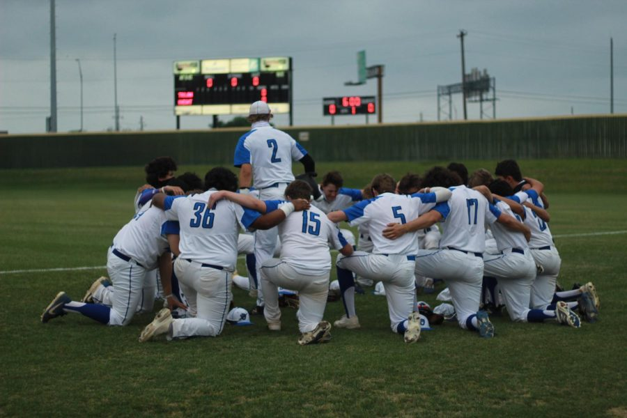 """Senior captain Ethan Vandament leads the varsity baseball team as they """"talk about it"""" before their rivalry game against Anderson on Tuesday April 16."""