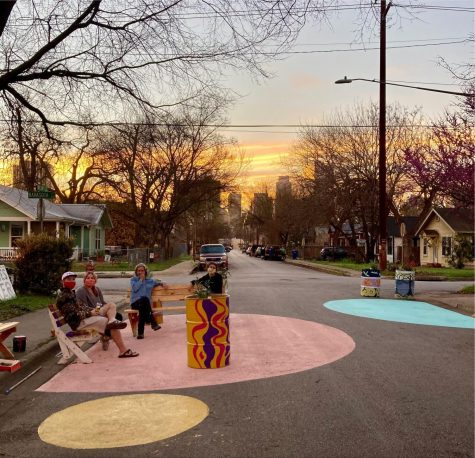 Three neighbors sit on self-painted benches in the street, after a community art event. This moment is an example of place-making to create a more comforting outdoor environment.