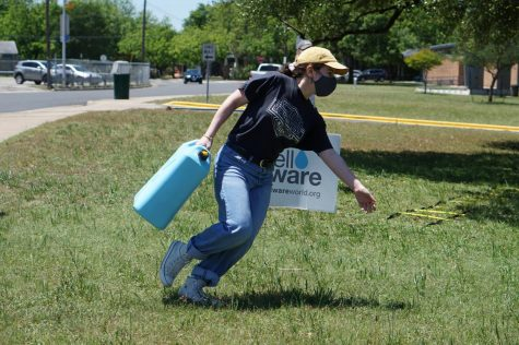 Senior PAL Bella Russo makes a sharp cut in the grass as she veers around the Well Aware sign nearing the halfway point of the water walk obstacle course.