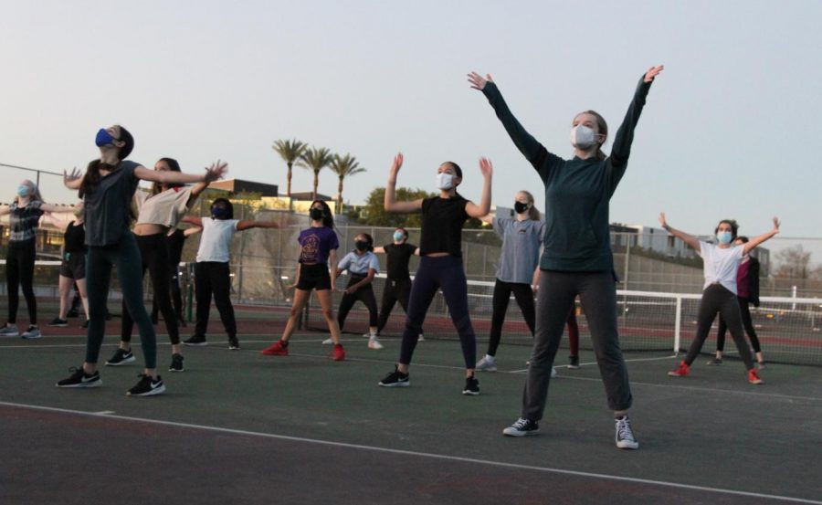 """Freshman Danielle Todd-Harris and other McCallum theater students gathered on Nov. 11 on the Mac tennis courts to learn song and dance in preparation for auditions for the spring musical, Urinetown. """"It felt good to do an in-person audition again,"""" Danielle said when looking back on this memory. After months without theater in her life, Danielle, sixth from the left in the white shirt, says that participating in her first McCallum production felt amazing and that it was just what she needed."""
