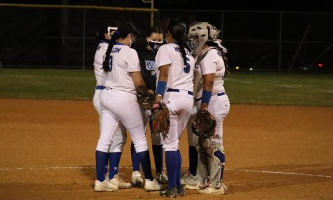 The varsity infield meets at the mound during the Knights