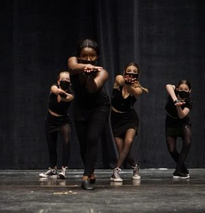"""In the jazz dance number, """"History Repeating,"""" Parker Mitchell, Wynter Winston, Maddie Hello and Samantha Bogle dance with the mindset that they are spies hunting their next target and looking for who might be targeting them. Winston said she was excited to perform this dance, choreographed by the B. Iden Payne Award-winning Sara Burke, because it was one she had learned the year before and was scheduled to perform it at the 2020 spring dance show. """"We had to put it on hold due to COVID,"""" Winston said. She said she didn't really have a favorite number in last weekend's show but rather enjoyed the whole experience. """"My favorite moment from this weekend overall was just being in the MAC again with all my dance friends. It was back to familiarity."""""""
