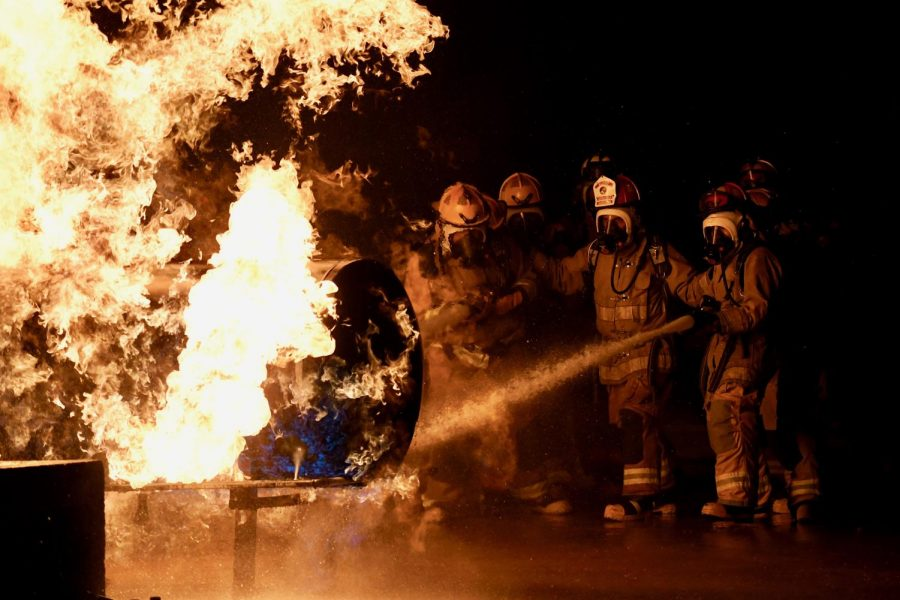 """WEEKEND FIRE DRILL: Students from the LBJ Fire Academy work their way towards a propane fire on Oct. 3, using fire hoses to control the blaze. The purpose of the drill wasn't to put out the fire, but to use the spray to get close enough to the propane tank to turn off its fuel source. Five McCallum seniors, John Hughes, Thomas Lucy, Tex Mitchell, Molly Odland and Will Russo, participated in the live fire skill day, where they put into practice what they've learned during the two year student-sharing program at LBJ High School. """"Being in the live fire gave me really intense adrenaline,"""" senior Molly Odland said. """"I was the head of my group, meaning I was in charge of directing the hose line at the fire while my group supported me from behind."""" Senior Will Russo, who also had the chance to lead the group, said that the drill felt like being in a hot car. """"It wasn't all that scary since you were with a bunch of people, but it was kind of intimidating because there was nothing in between you and the fire but water,"""" Russo said, before adding that """"the propane smelled kind of like pumpkin spice."""" The next live fire the students will tackle will be a class A structure fire later in the month, before beginning EMT certification training in the spring."""