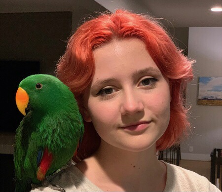 Cinematic arts major Emmylou Stephens stands with her pet eclectus parrot, Sprout. After owning Sprout for the entirety of the COVID-19 pandemic, he has become one of Emmylou's closest companions.