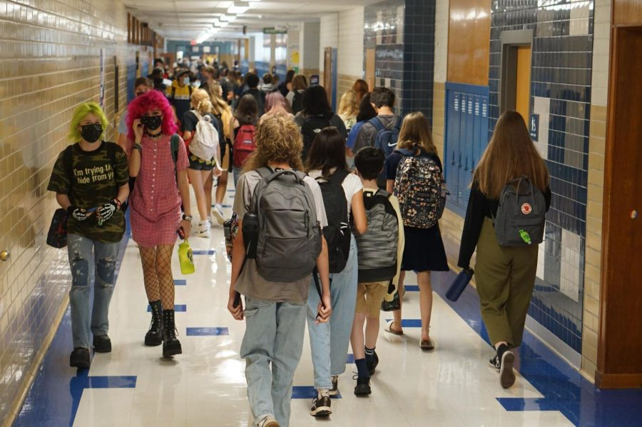 """CROWDSOURCING: Arwen Frederiksen (far left) walks down the hallway before school starts to re-familiarize themselves with the campus. """"[The hallways] were definitely busier than I expected,"""" Frederiksen said. After almost a year and a half of virtual learning, Frederiksen expresses how they are simply happy to be around other people once again. """"I haven't seen a bunch of my just school friends in forever,"""" Frederiksen said. """"It was great."""" Reporting by Alysa Spiro."""