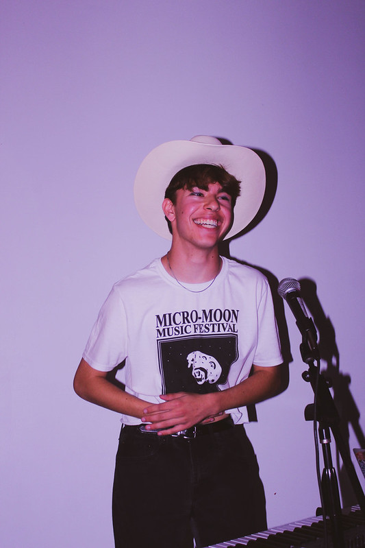 """MASSIVE NIGHT OF MICRO-MUSIC: Sporting his festival tee, junior Jay Mathias dances on stage at the Micro-Moon concert held this fall at the Austin Film School. The festival showcased featured Mathias as well as a variety of other musicians at Mac including Marlee Foster, Will Dooley, and The Point. """" I had always wanted to perform music, sort of a pipe dream type of thing, and we threw our first concert and it just felt so great to do that, even if it was a little rough,"""" Mathias recalled. """"That's when I realized: I have to do this."""" Photo by Risa Darlington-Horta."""