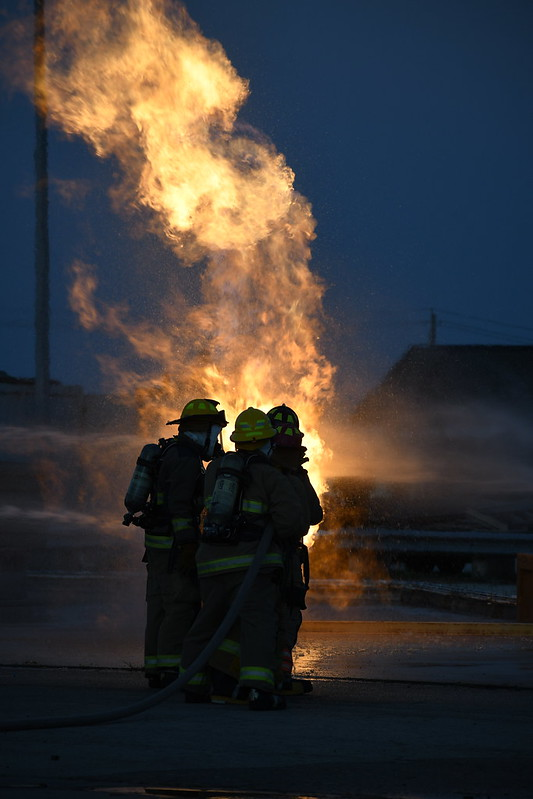 """Students from the LBJ Fire Academy work their way towards a propane fire, using fire hoses to control the blaze. The purpose of the drill wasn't to put out the fire, but to use the spray to get close enough to the propane tank to turn off its fuel source. Five McCallum seniors, John Hughes, Thomas Lucy, Tex Mitchell, Molly Odland and Will Russo, participated in the live fire skill day, where they put into practice what they've learned during the two year student-sharing program at LBJ High School. """"Being in the live fire gave me really intense adrenaline,"""" senior Molly Odland said. """"I was the head of my group, meaning I was in charge of directing the hose line at the fire while my group supported me from behind."""" Senior Will Russo, who also had the chance to lead the group, said that the drill felt like being in a hot car. """"It wasn't all that scary since you were with a bunch of people, but it was kind of intimidating because there was nothing in between you and the fire but water,"""" Russo said."""