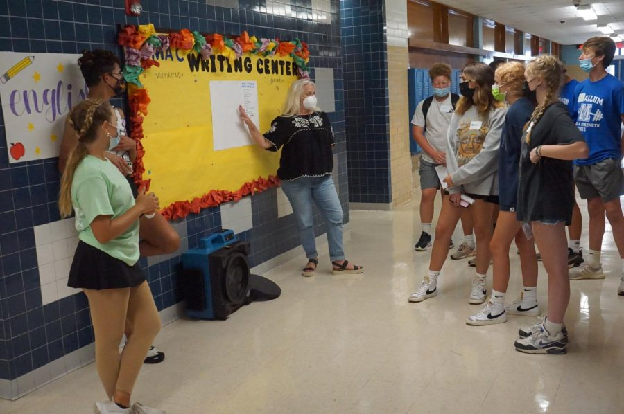Junior+Sophia+Kramer+and+senior+Bobby+Currie+help+English+teacher+Diana+Adamson+give+a+tour+of+the+English+hall+at+the+freshman+orientation.+Everyone+was+masked+in+compliance+with+the+Austin+ISD+mask+mandate+in+place.