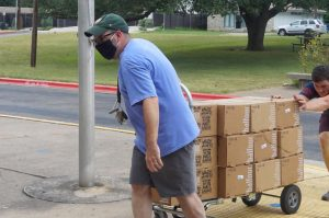 Co-adviser David Winter helps unload the yearbooks on campus today. Distribution will be held on Monday, Aug. 9.