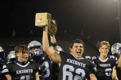 Senior center Braeden Price hoists the Taco Shack Trophy after the Knights 14-13 victory over the Trojans allowed the Knights to bring the cherished golden football to Sunshine Drive for the first time since 2018.