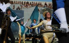 """AND CUT: Members of the color guard eagerly motion their hands towards their captain, Natalie Nagy, in the closing moments of """"Mirage."""" During the Capital City Marching Festival, the guard earned a second place title in the preliminary round. """"We crushed it,"""" color guard member Ella Jones said. Reporting by Grace Vitale."""